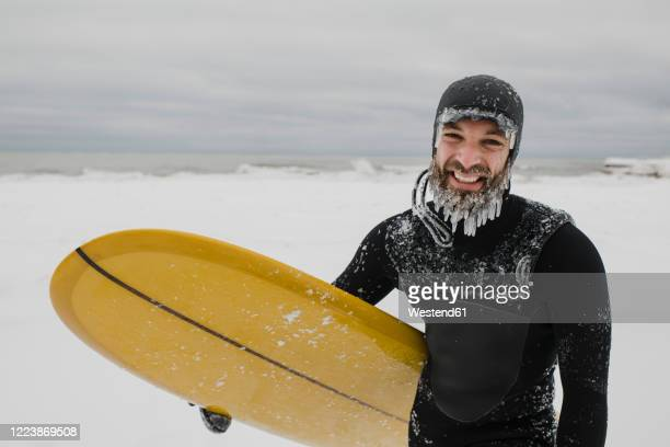 surfer with surfboard in snow in ontario, canada - froid humour photos et images de collection
