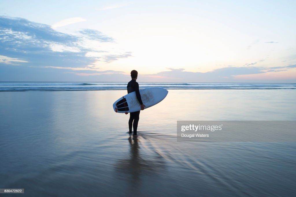 Surfer with surfboard looking out to sea at dusk. : Stock Photo