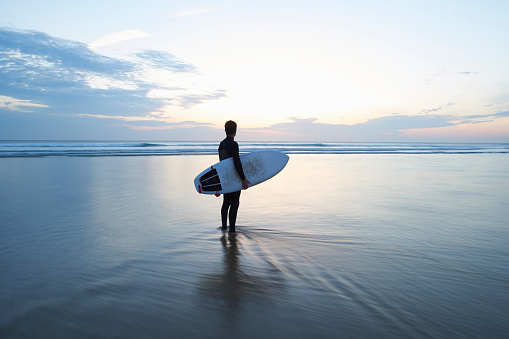 Surfer with surfboard looking out to sea at dusk. - gettyimageskorea