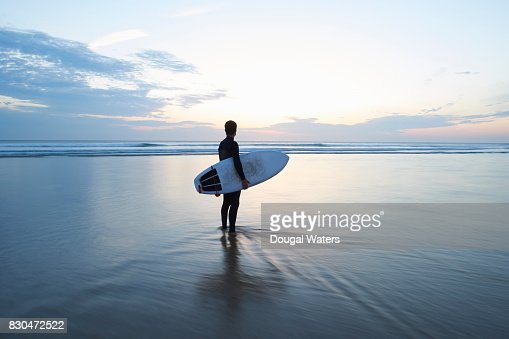 Surfer with surfboard looking out to sea at dusk.