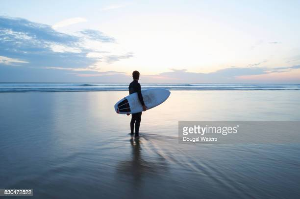 surfer with surfboard looking out to sea at dusk. - libertà foto e immagini stock