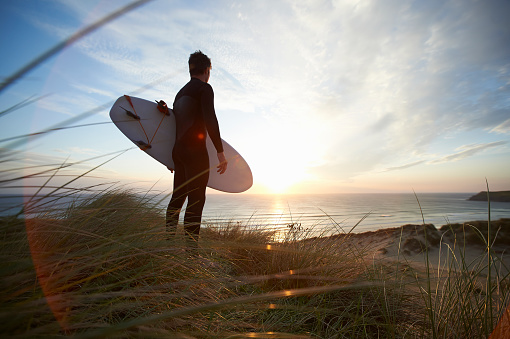 Surfer with surfboard looking out to sea from beach. - gettyimageskorea