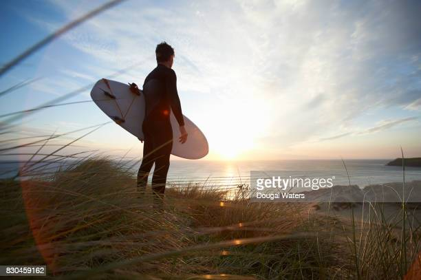 surfer with surfboard looking out to sea from beach. - dougal waters stock pictures, royalty-free photos & images