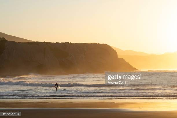 surfer with surfboard on beach during sunset. spain - ビスカヤ県 ストックフォトと画像