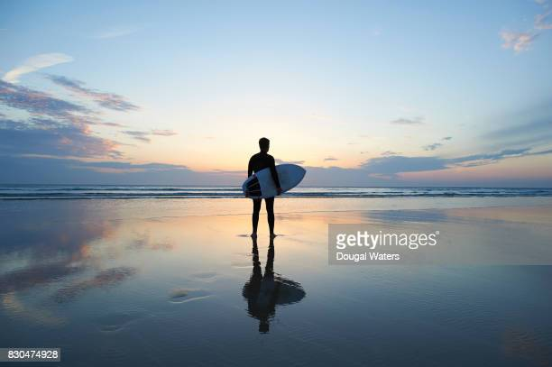surfer with surfboard on deserted beach at sunset. - surf stock pictures, royalty-free photos & images