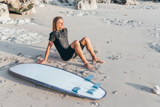 Surfer with surfboard on the beach. Active lifestyle.