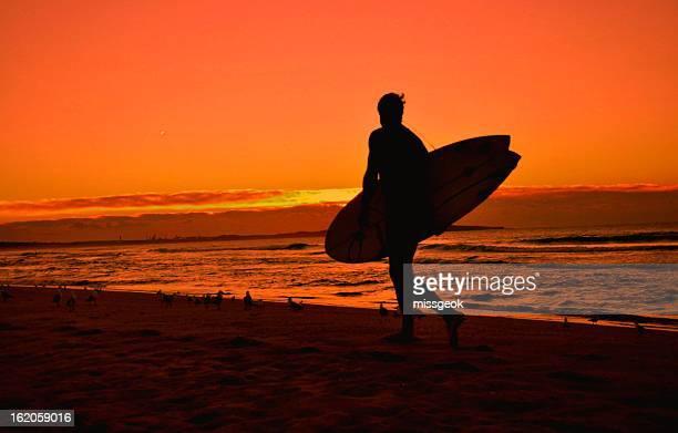 Surfer with surfboard walking on beach