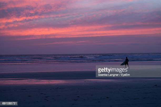 surfer with surfboard walking on shore at beach against sky during sunset - marina langner foto e immagini stock