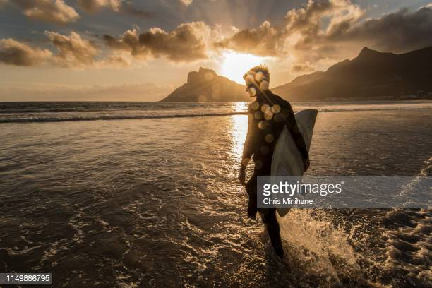surfer with surfboard with dramatic sun flare - aquatic sport stock pictures, royalty-free photos & images