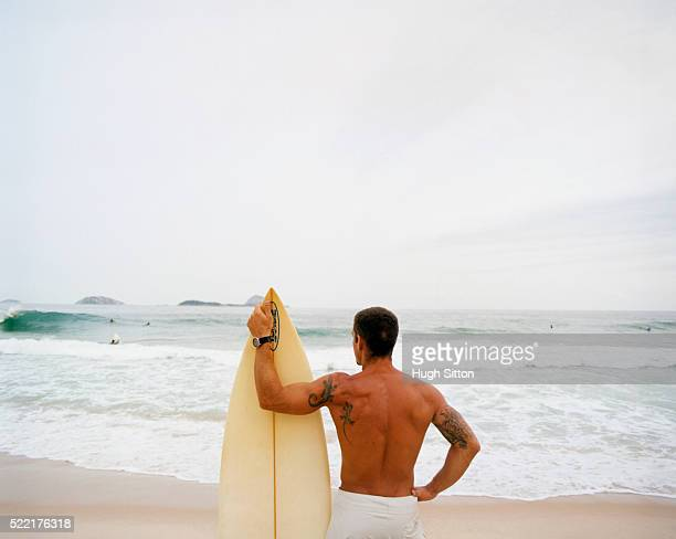 surfer with tattoos on the beach - hugh sitton stock-fotos und bilder