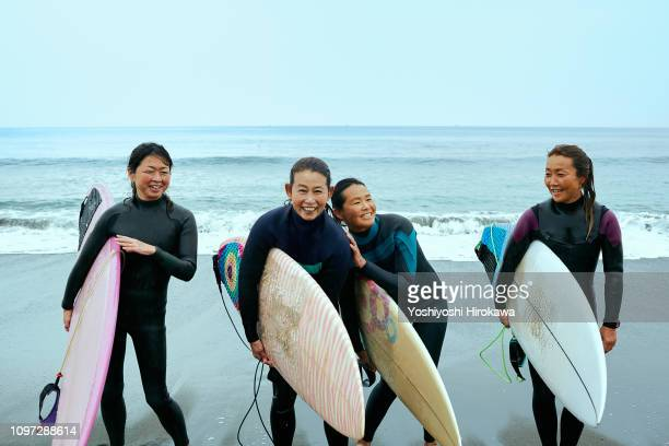 Surfer women are laughing in front of ocean