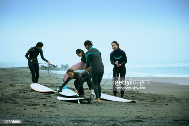surfer women are talking in front of wave in the rain - 茅ヶ崎市 ストックフォトと画像
