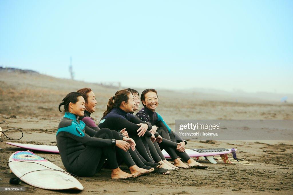 Surfer women are talking on beach in the rain : Stock Photo