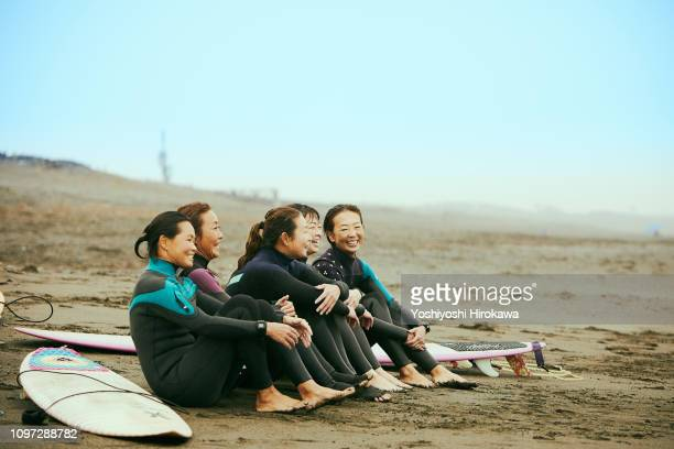 Surfer women are talking on beach in the rain