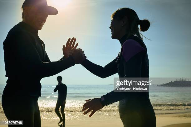 Surfer women hand touch to coach in morning coast.