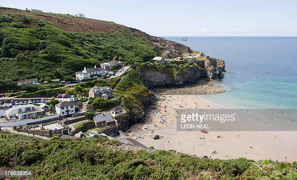 Surfers and sunbathers enjoy the warm weather in St Agnes near Truro in Cornwall, southwestern England on August 7, 2013. Mike Proudfoot, CEO of...
