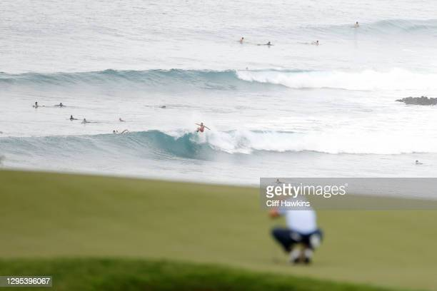 Surfers are seen as Justin Thomas of the United States lines up a putt on the 11th green during the second round of the Sentry Tournament Of...