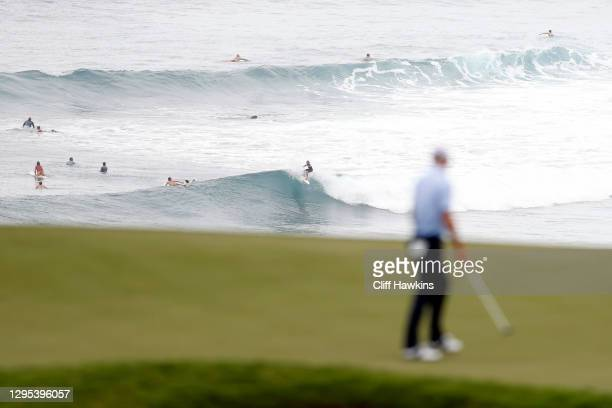 Surfers are seen as Justin Thomas of the United States walks on the 11th green during the second round of the Sentry Tournament Of Champions at the...