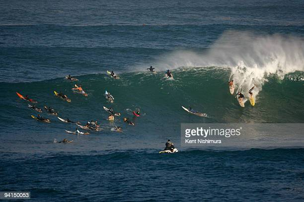 Surfers are seen riding waves during precontest surf before the 2009 Eddie Aikau BigWave Invitational on December 8 2009 at Waimea Bay in Waimea...