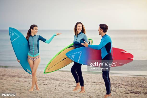 Surfers are standing on the beach and make fun