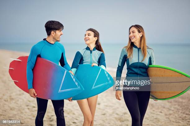 Surfers are walking on the beach and make fun