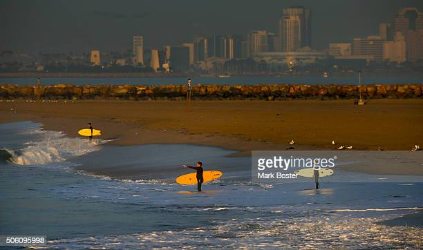Surfers at Seal Beach take off on their dawn patrol with the city of Long Beach in the background January 21 2016 in Seal Beach California