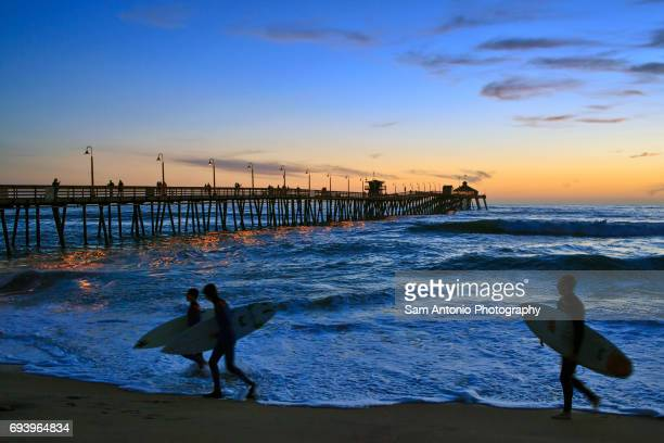 Surfers at sunset at the Imperial Beach Pier in San Diego, California, USA.