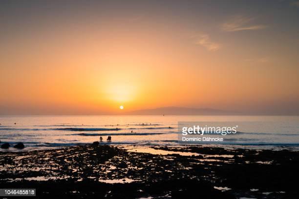surfers at sunset in adeje's coast, south of tenerife, with la gomera island above horizon - dähncke fotografías e imágenes de stock