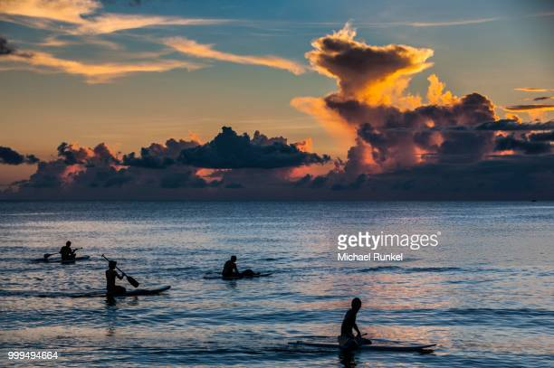 surfers at sunset in guam, us territory, central pacific - guam stock pictures, royalty-free photos & images