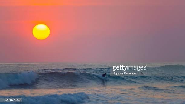 surfers at sunset in playa carmen, costa rica - península de nicoya fotografías e imágenes de stock