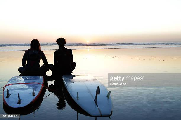 surfers at sunset , sitting on surfboard