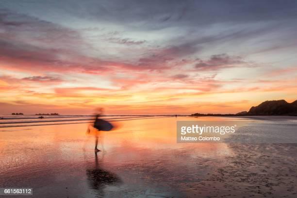 surfers at sunset walking on beach, playa guiones, costa rica - península de nicoya fotografías e imágenes de stock