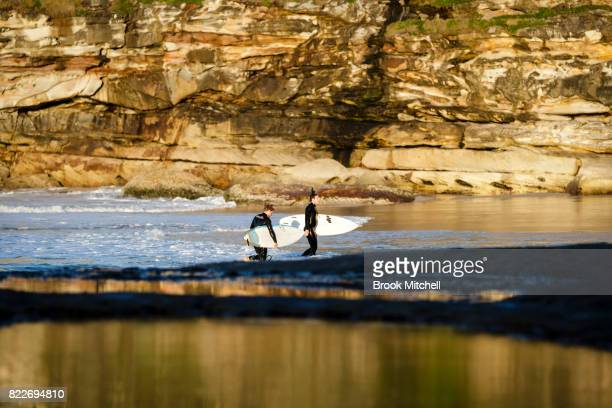 Surfers at Tammaramma on July 26 2017 in Sydney Australia Sydney is on track to have its warmest winter weekend in 27 years with temperatures...
