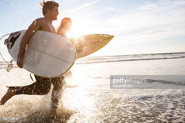 surfers at the beach - surf stock pictures, royalty-free photos & images