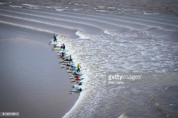 Surfers attempt to ride the Severn Bore as it passes in Newnham on Severn on February 2 2018 in Gloucestershire England The bore which follows this...