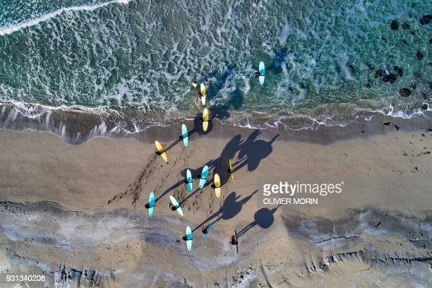 TOPSHOT Surfers attend a a surfing course on March 10 2018 in Unstad northern Norway Lofoten islands within the Arctic Circle as air temperature...