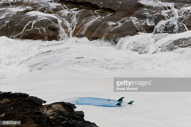 A surfers boad washes up against the cliffs during Cape Fear on June 6 2016 in Sydney Australia