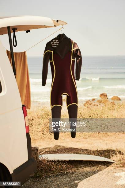 A surfer's camper van with a drying wetsuit hanging outside at the coast.