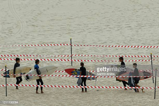Surfers carry their boards on Bondi Beach after it reopened following a five week closure in Sydney on April 28 amid the COVID19 novel coronavirus...