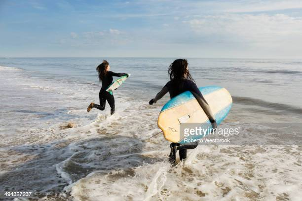 surfers carrying boards in waves - virginia beach stock photos and pictures