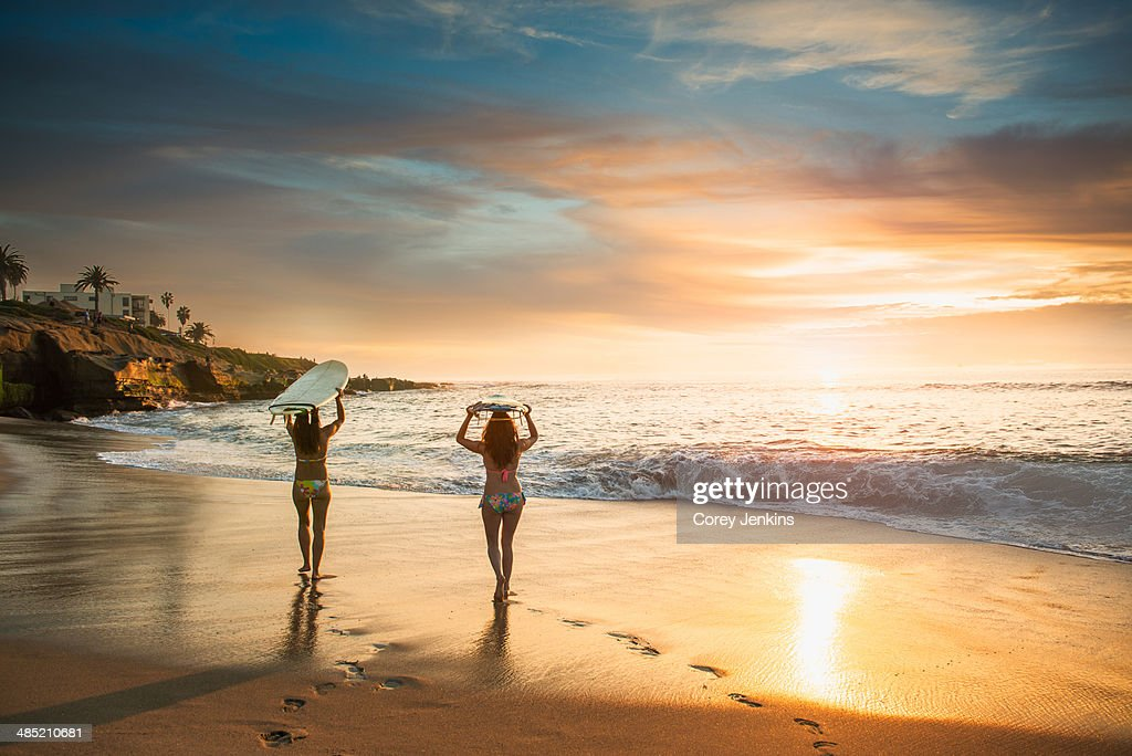 Surfers carrying surf board, walking along beach : Stock Photo
