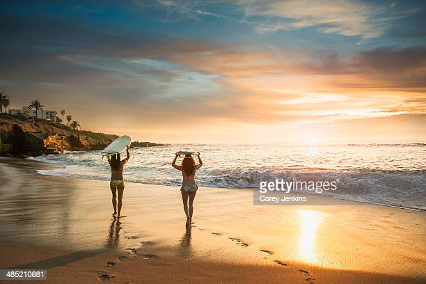 surfers carrying surf board, walking along beach - california stock pictures, royalty-free photos & images