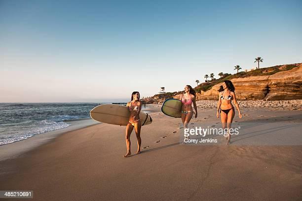 Surfers carrying surf boards, walking along beach