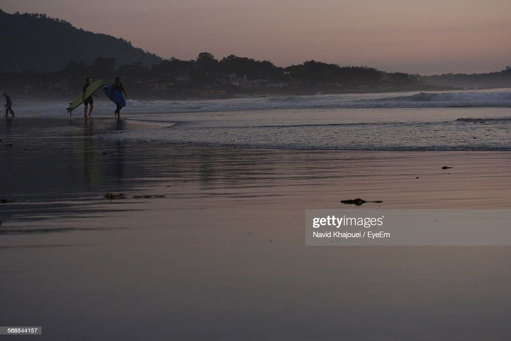 Surfers Carrying Surfboards On Beach During Sunset : Stock Photo