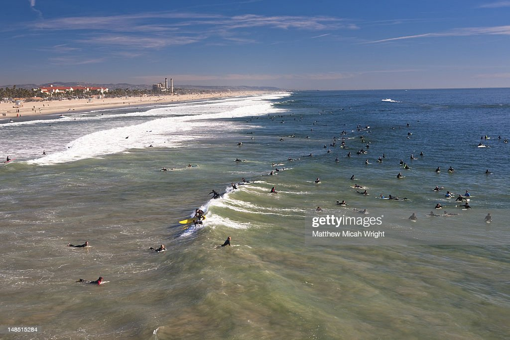 Surfers catching waves after memorial paddle out commemorating pro surfer Andy Irons by Huntington Beach Pier. : Stock Photo