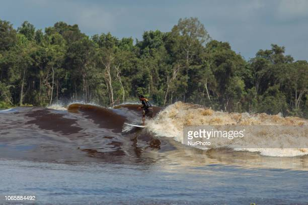 Surfers compete during Bono festival at Kampar river in Teluk Meranti village on November 24 2018 in Sumatra Indonesia The Bono tidal wave occurs...