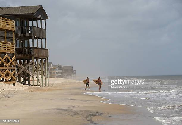 Surfers David Grimes and William Troy walk down the beach while mandatory evacuation orders are in effect for Hatteras Island July 3 2014 in Rodanthe...