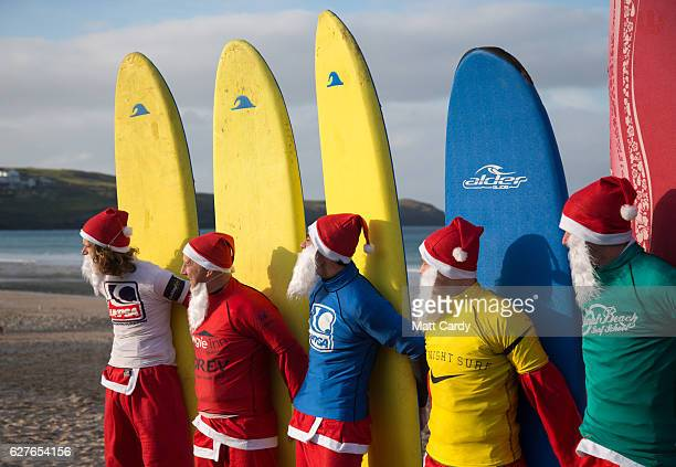 Surfers dressed as Santa pose for a photograph before competing in a heat during the annual Surfing Santa as part of the Santa Run and Surf 2016 at...
