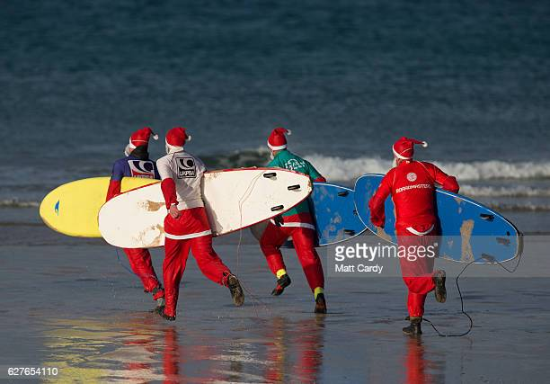 Surfers dressed as Santa run to sea as they compete in a heat during the annual Surfing Santa as part of the Santa Run and Surf 2016 at Fistral Beach...