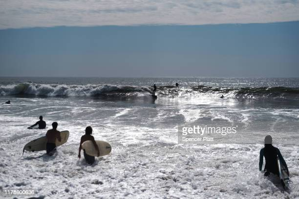 Surfers enjoy the large waves and unseasonably warm weather as park rangers continue to search for two missing swimmers on October 02 2019 in New...